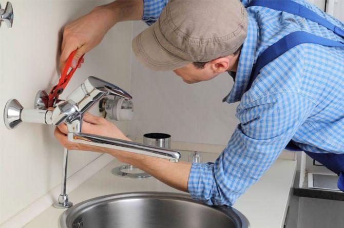 Encanador conserta torneira